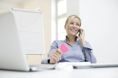 Businesswoman holding paperheart. Businesswoman flirting on phone with paperheart in her hand Stock Image
