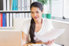 businesswoman holding papers at office desk Stock Image
