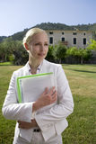 Businesswoman holding paperwork in grass behind manor Royalty Free Stock Photo