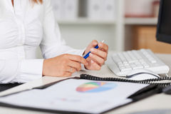 Businesswoman Holding Pen At Office Desk Stock Photography