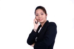 Businesswoman holding a phone. A confident businesswoman holding a phone against white background Royalty Free Stock Images