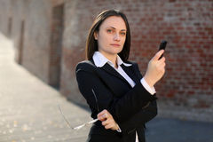Businesswoman holding phone and glasses. In front of a brick wall Stock Image