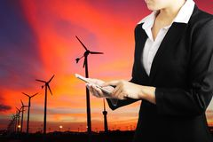 Businesswoman holding smart phone for industry energy business c. Businesswoman holding phone with wind turbine generator electricity background, Industry energy royalty free stock photo