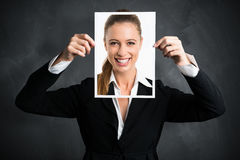 Businesswoman holding a picture of herself, showing positive attitude. As a facade royalty free stock image