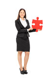 Businesswoman holding a piece of a puzzle Stock Photo