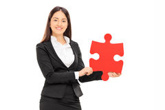 Businesswoman holding a piece of a puzzle Stock Images