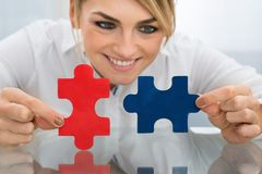 Businesswoman holding pieces of jigsaw puzzle Stock Photo