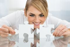 Businesswoman Holding Pieces Of Jigsaw Puzzle Stock Photos