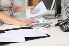 Businesswoman Holding Piechart While Using Calculator At Desk Royalty Free Stock Image