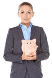Businesswoman holding a piggy bank Stock Images