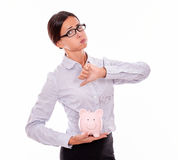 Businesswoman holding piggy bank with disapproval. Businesswoman holding pink porcelain piggy bank with disapproval and a thumb down gesture wearing her hair Royalty Free Stock Photos