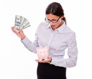 Businesswoman holding piggy bank and dollar bills Stock Images