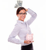 Businesswoman holding piggy bank and dollar bills Stock Photos