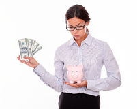 Businesswoman holding piggy bank and dollar bills Royalty Free Stock Images