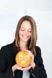 Businesswoman Holding Piggy Bank In Office Stock Photo