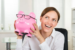 Businesswoman Holding Piggybank With Eyeglasses Royalty Free Stock Image