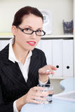 Businesswoman holding pills and water. Stock Photography
