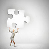 Businesswoman holding puzzle element Stock Photo
