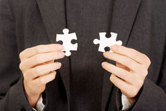 Businesswoman holding puzzle pieces. Businesswoman connecting two puzzle pieces royalty free stock images