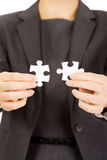Businesswoman holding puzzle pieces. Businesswoman connecting two puzzle pieces stock images