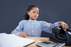 Businesswoman holding receiver of land line phone. While sitting at desk against black background Royalty Free Stock Photo