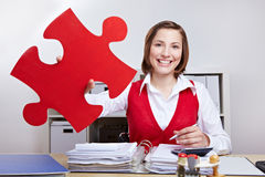 Businesswoman holding red jigsaw puzzle piece. Attractive businesswoman holding oversized red jigsaw puzzle piece Stock Photo