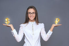 Businesswoman holding ruble and dollar symbols or signs. Stock Image