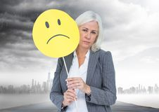 Businesswoman holding a sad face in front of her face with rain clouds in background Royalty Free Stock Photos
