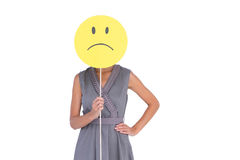 Businesswoman holding sad smiley face Stock Images