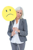 Businesswoman holding sad smiley face Royalty Free Stock Photos