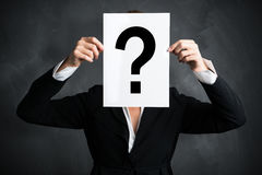Businesswoman holding a sheet of paper with a questionmark Stock Images