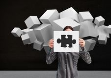 Businesswoman holding sheet of paper showing jigsaw puzzles and white cubes in backgrounds. Digital composition of businesswoman holding sheet of paper showing Royalty Free Stock Photos