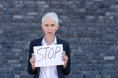 Businesswoman is holding a sign. In front of herself with the inscription STOP stock photography