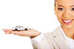 Businesswoman holding small car on palm. Stock Photo
