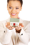 Businesswoman holding small house on palm. Royalty Free Stock Image