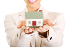 Businesswoman holding small house on palm. Royalty Free Stock Images