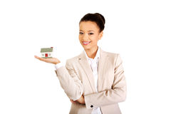 Businesswoman holding small house on palm. Stock Photo