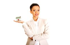 Businesswoman holding small house on palm. Royalty Free Stock Photography