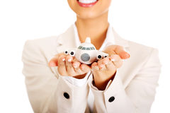 Businesswoman holding small plane on palm. royalty free stock images