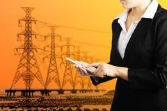 Businesswoman holding smart phone for industry energy business c. Businesswoman holding phone with high voltage electric transmission tower energy pylon stock images