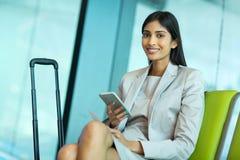 Businesswoman holding smart phone. Smiling indian businesswoman holding smart phone at airport Royalty Free Stock Image