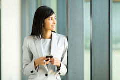 Businesswoman holding smart phone. Thoughtful indian businesswoman holding smart phone in office Stock Images