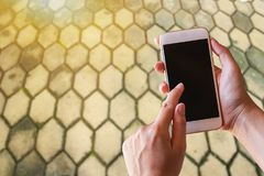 Businesswoman holding smartphone with blurred background. Blank space for graphic display montage Stock Photos