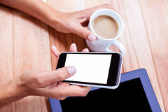 Businesswoman holding smartphone and coffee cup Stock Photos