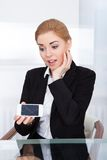 Businesswoman holding smartphone with cracked screen stock photography
