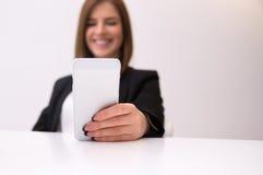 Businesswoman holding smartphone. Focus on smartphone Stock Photos