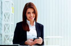 Businesswoman holding smartphone on her workplace Stock Image