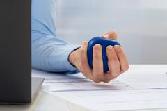 Businesswoman holding stress ball Royalty Free Stock Photos