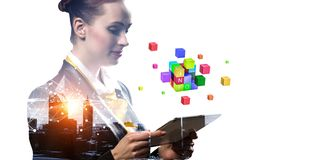 Businesswoman holding a tabalet with cube puzzle. Mixed media stock photo