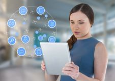 Businesswoman holding tablet with apps icons in bright space hall Stock Image